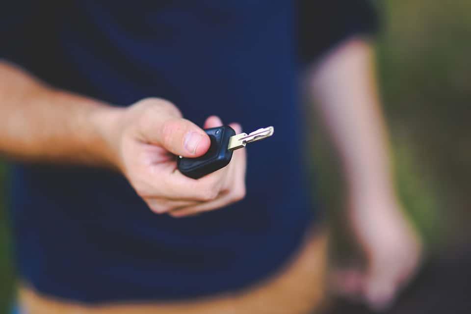 Un homme tient une clé de voiture dans sa main