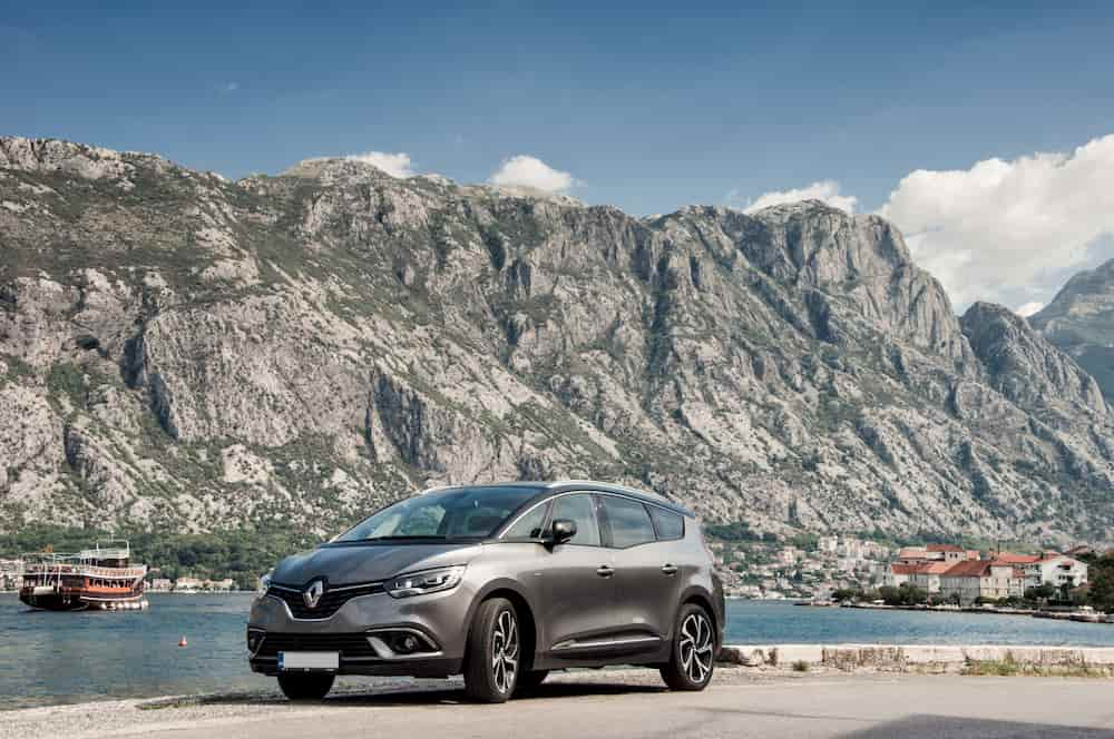 Renault grand scenic au bord d'un lac et des montagnes