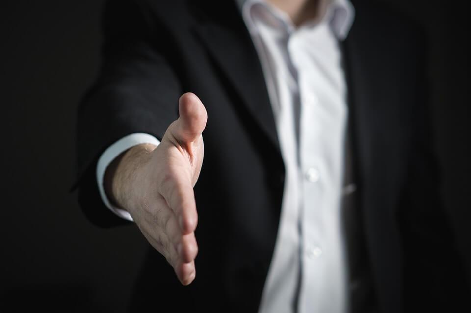 Un vendeur tend sa main vers vous pour vous saluer